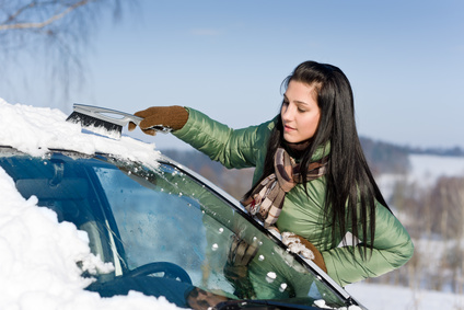 Woman maintaining her winter vehicle